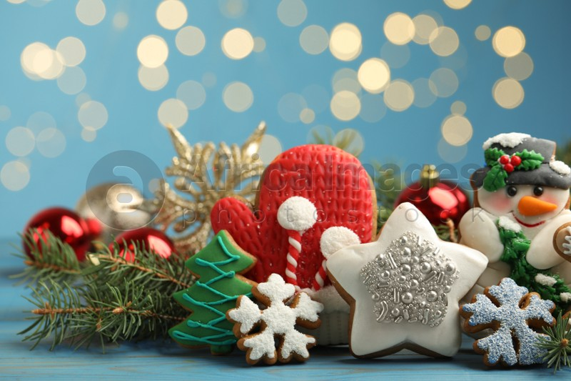 Sweet Christmas cookies and decor on light blue table against blurred festive lights
