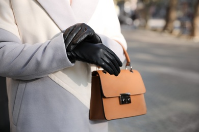 Woman with leather gloves and stylish bag on city street, closeup