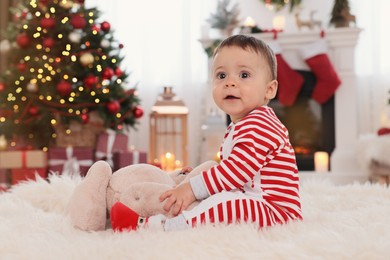 Cute baby playing with toy on floor in room decorated for Christmas