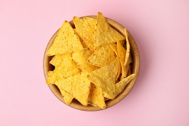 Wooden bowl with tasty Mexican nachos chips on pink background, top view
