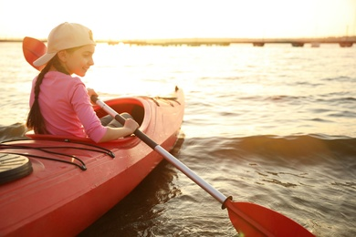 Happy girl kayaking on river. Summer camp activity