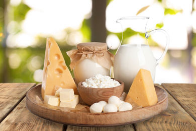 Set of different dairy products on wooden table outdoors