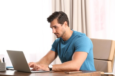 Handsome young man working with laptop at table in office
