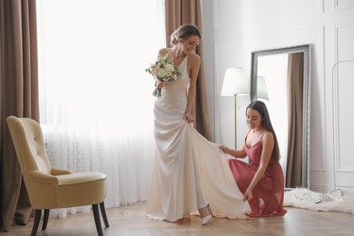 Gorgeous bride in beautiful wedding dress and her friend near mirror in room