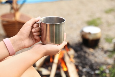 Young woman with mug near bonfire outdoors, focus on hands. Camping season