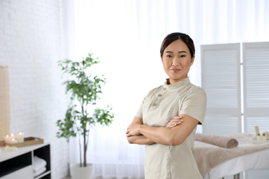 Portrait of young Asian masseuse in spa salon. Space for text