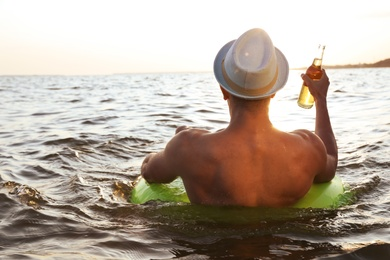 Young man with drink on inflatable ring in sea