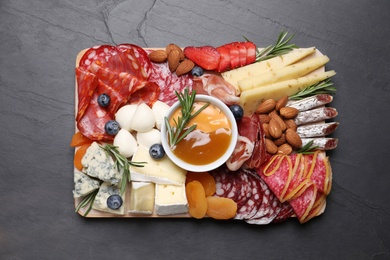 Wooden plate with different delicious snacks on black table, top view