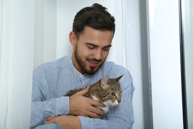 Man with tabby cat near window at home. Friendly pet