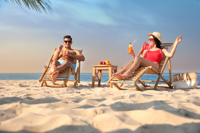 Couple with drinks resting on sunny beach at resort