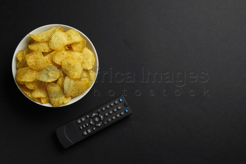 Modern tv remote control and chips on black background, flat lay. Space for text