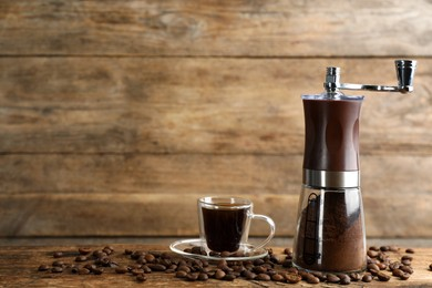Manual coffee grinder with powder, beans and cup of drink on wooden table. Space for text