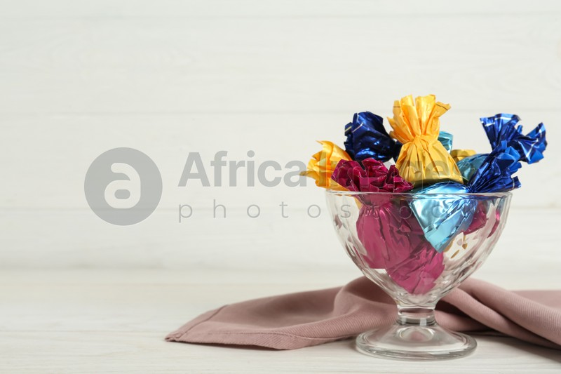 Candies in colorful wrappers on white wooden table, space for text