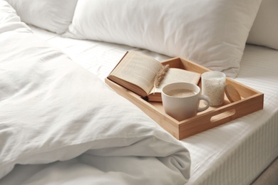 Cup of aromatic coffee, book and candle on bed with soft blanket indoors