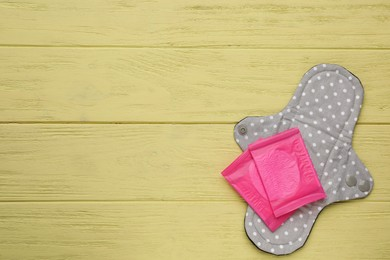 Disposable and reusable cloth menstrual pads on yellow wooden table, top view. Space for text