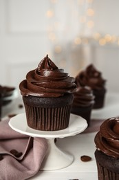 Dessert stand with delicious chocolate cupcake on white table against blurred lights