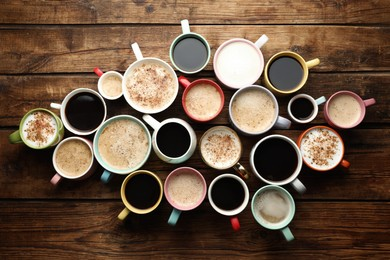 Many cups of different coffees on wooden table, flat lay