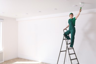 Worker painting ceiling with white dye indoors, space for text
