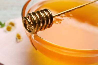 Tasty honey in glass bowl and dipper on table, closeup