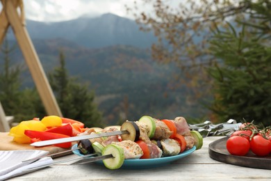 Metal skewers with raw marinated meat and vegetables on wooden table against mountain landscape