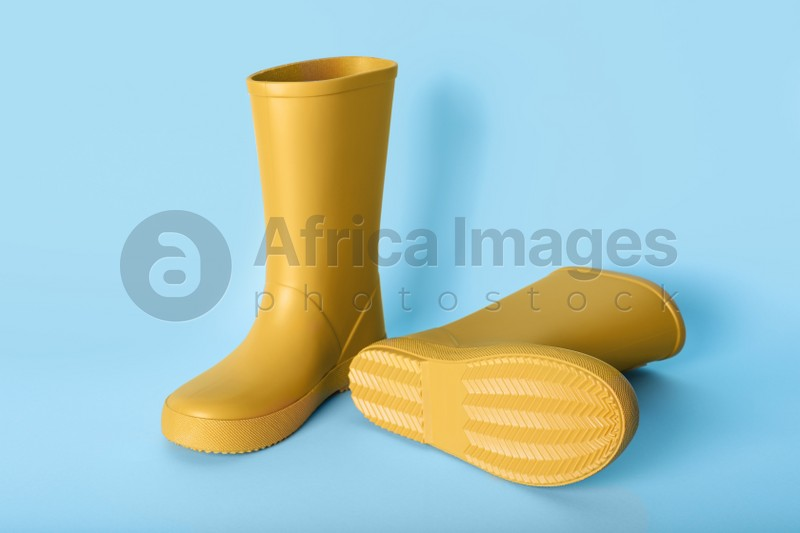 Pair of yellow rubber boots on light blue background