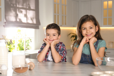 Cute little children at table with cooking ingredients in kitchen