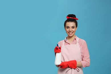Young housewife with detergent on light blue background, space for text
