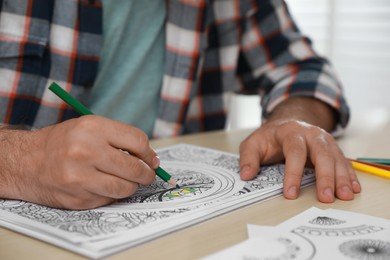 Man coloring antistress picture at table indoors, closeup