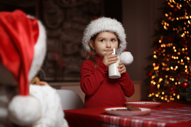 Cute little child with glass of milk at table in dining room. Christmas time