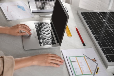 Woman working on house project with solar panels at table in office, closeup