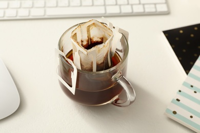 Glass cup with drip coffee bag on white table, closeup