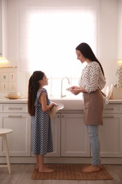 Mother and daughter wiping dishes together in kitchen