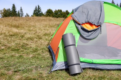 Grey sleeping bag on camping tent and mat outdoors, space for text