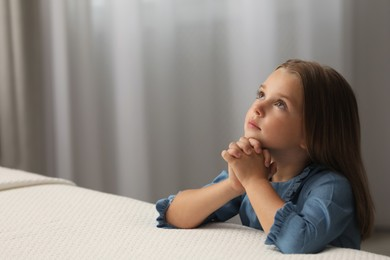 Cute little girl with hands clasped together saying bedtime prayer in bedroom. Space for text