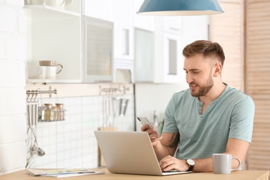 Young man using mobile phone and laptop at table in kitchen