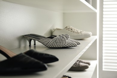 Storage rack with stylish women's shoes indoors, closeup