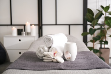 Towels, aroma lamp, orchid flower and stones on couch in spa salon