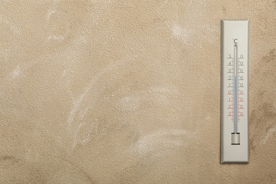Weather thermometer on beige wall. Space for text