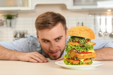 Young hungry man and huge burger on table