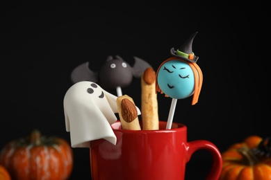 Different cake pops in cup decorated as monsters, closeup. Halloween treat