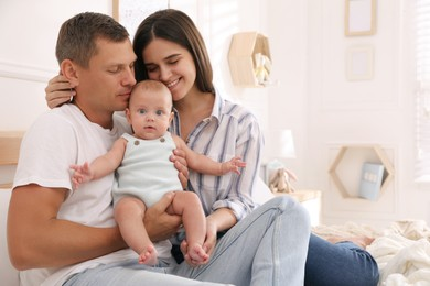 Happy family with their cute baby on bed at home