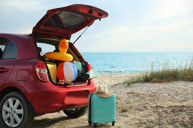 Red car luggage on beach, space for text. Summer vacation trip