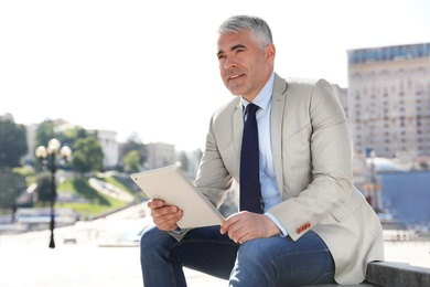 Portrait of handsome businessman with tablet in city, space for text
