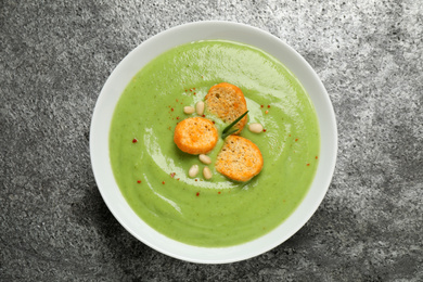 Tasty homemade zucchini cream soup on grey table, top view
