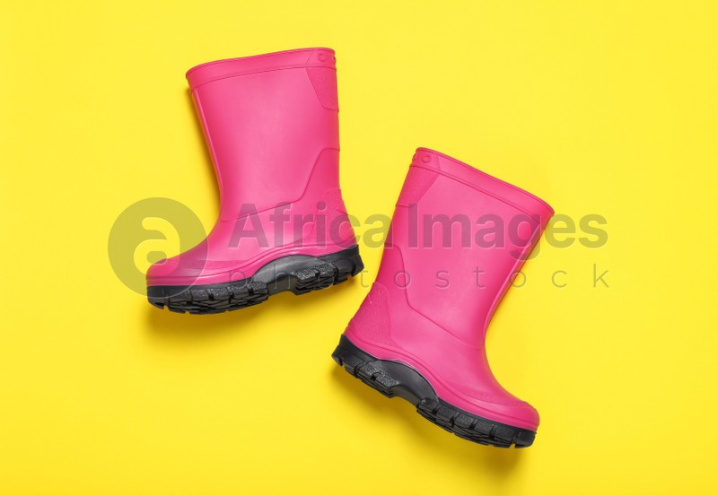 Pair of bright pink rubber boots on yellow background, top view