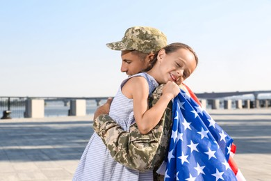 Soldier with flag of USA and his little daughter hugging outdoors, space for text