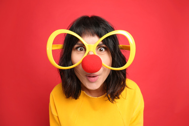 Funny woman with large glasses and clown nose on red background. April fool's day
