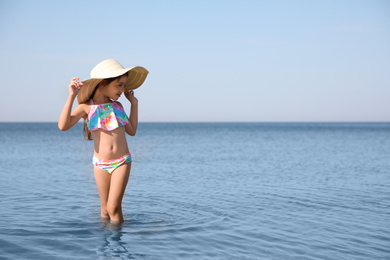 Cute little child with straw hat in sea on sunny day. Beach holiday