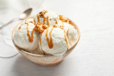 Tasty ice cream with caramel sauce and popcorn in bowl on table