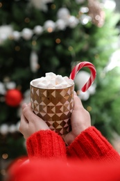 Woman with cup of delicious hot drink near Christmas tree indoors, closeup
